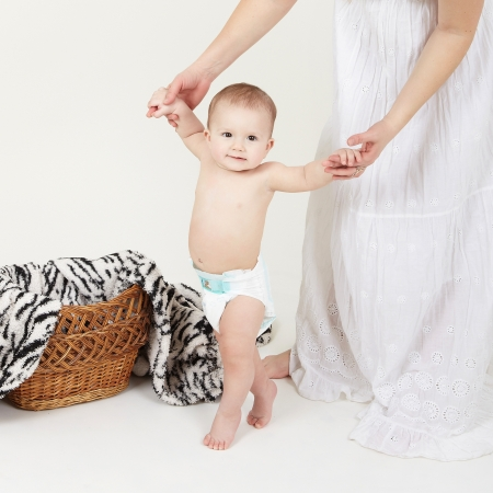 Portrait of cute little boy stand with mother help over white  photo