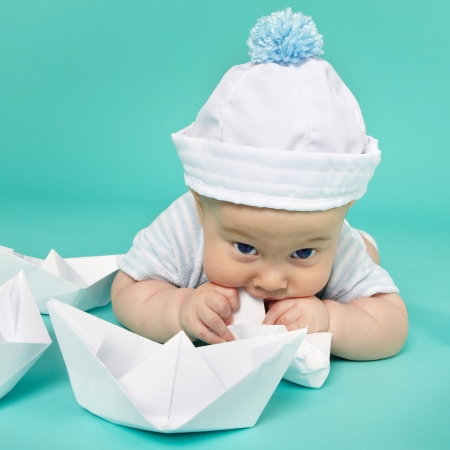 Portrait of cute little boy plays with toy ship. Sea theme  photo