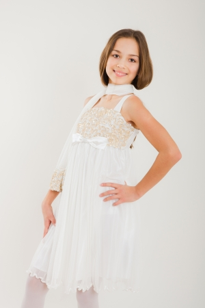 Portrait of a beautiful happy girl posing in elegant dress  Studio shot over white background  photo