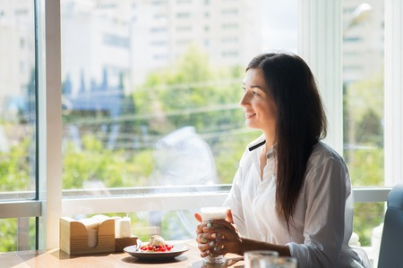 Beautiful smiling young woman in cafe near the window with coffee and delicious cake.