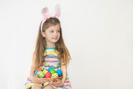 Cute little girl wearing bunny ears holding painted Easter eggs and smiling on a white background.