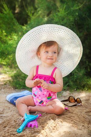 Baby girl playing on beach.