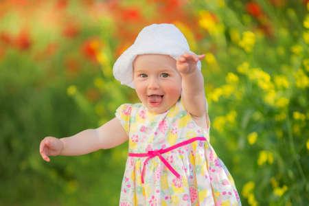 Portrait of a beautiful little girl having fun in field of red poppy flowers in spring. Archivio Fotografico