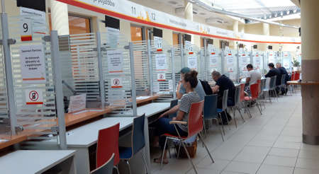Warsaw, Poland - July 21, 2020: Clients wearing COVID masks being served at the municipal car registration office