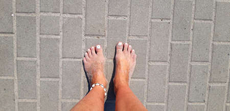 Tanned and sandy feet with white nail varnish and seashell anklet on the concrete background