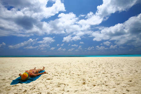 Young women is sunburning on the coral sandy beach Stock Photo - 3146012