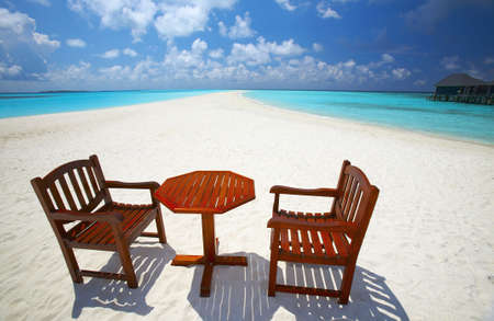 Two chairs and one table are on the coral sandy beach, Maldives Stock Photo