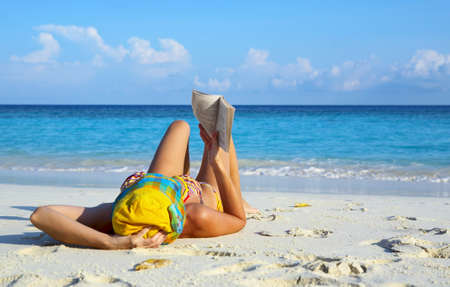 Young women is reading on coral beach, Maldives Stock Photo