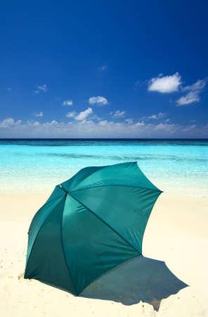 Green umbrella is on a sandy beach Stock Photo - 12621269