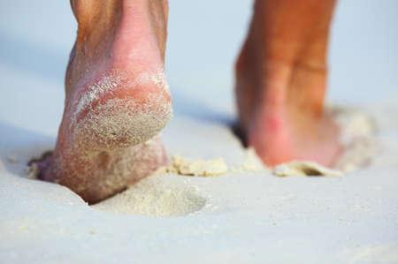 descalza: Las mujeres se van en una playa de arena de coral