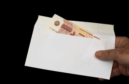 Russian roubles in white envelope, isolated on a black background photo