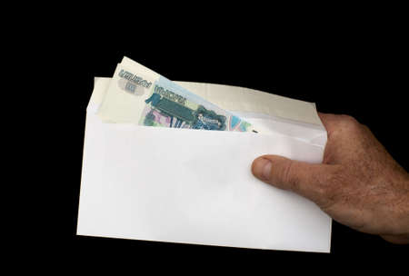 roubles: Russian roubles in white envelope, isolated on a black background