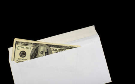 payola: American dollars in white envelope, isolated on a black background Stock Photo