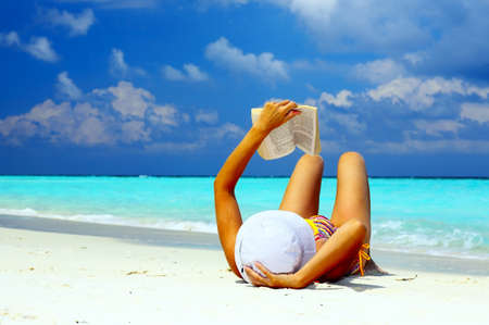 Young women is reading on the coral beach, Maldives Stock Photo