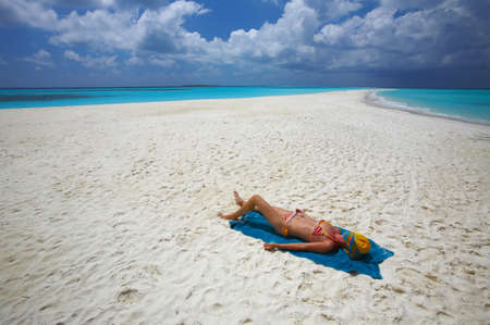 Young women is sunburning on the infinity coral sandy beach photo