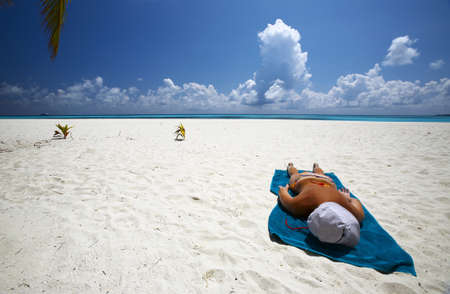 Young women is sunburning on the coral sandy beach, Maldives photo