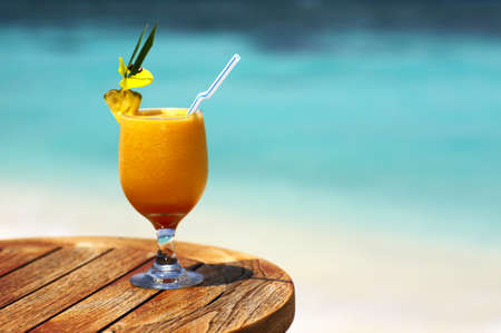 Bocal of fruity cocktail on a beach table Stock Photo
