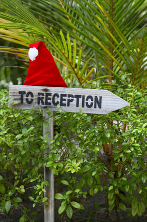 Funny wooden pointer to reception of a tropical hotel with christmas hat, Maldives photo