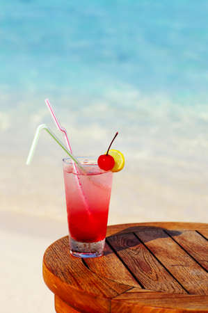 Refreshing cocktail on a beach table
