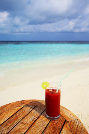 Glass of tomato juice on a beach table photo