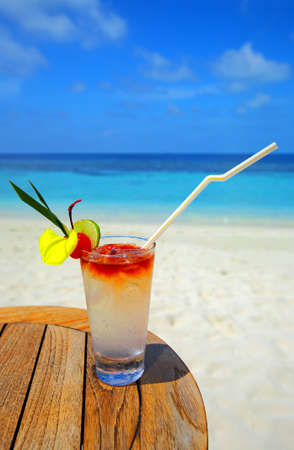Refreshing cocktail on a beach table photo
