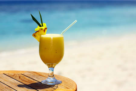 pineapple  glass: Bocal of fruity cocktail on a beach table Stock Photo