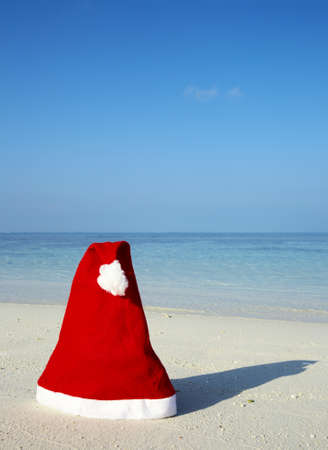 Christmas hat on a white sandy beach in the Indian Ocean, Maldives photo
