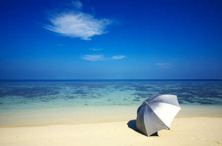 argent: Argent umbrella is on a sandy beach