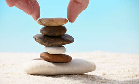 Woman is assembling stones on a coral sandy beach