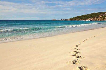 Lonely footprints are on sandy beach, Seychelles, La Digue island
