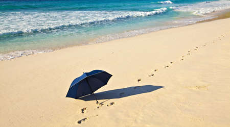 Blue umbrella is on a sandy beach Stock Photo - 13148300