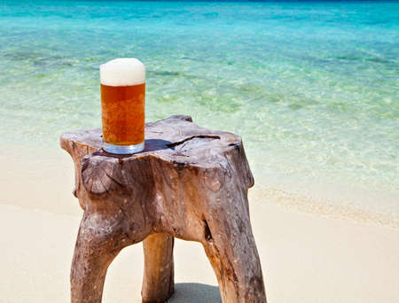 Glass of beer is on original beach table Stock Photo