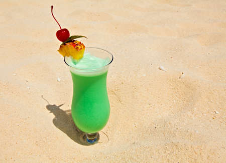bocal: Bocal of fruity cocktail is on a sandy beach
