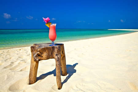 Bocal of cocktail is on original  beach table is made from trunk of tree photo