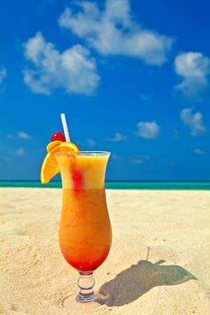 cocteles de frutas: Bocal del coctel con sabor a fruta se encuentra en una playa de arena