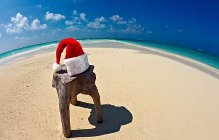 Santa hat is on an original stool  is made from trunk of tree , Maldives beach photo