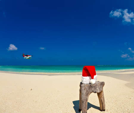 Santa hat is on an original stool  is made from trunk of tree with seaplane, Maldives beach photo