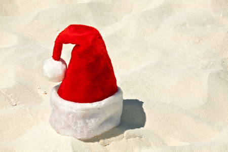 Santa hat is on a coral sandy beach photo