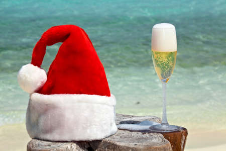 Bocal of champagne is on original  beach table is made from trunk of tree with Santa hat photo