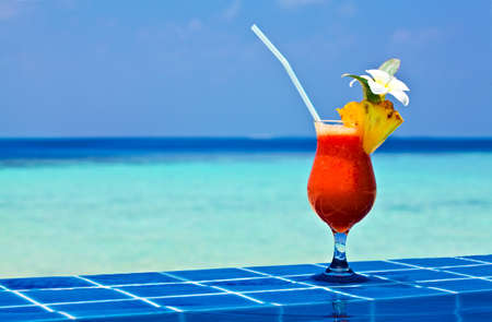 Glass of papaw juice is on edge of pool made from glazed tile  in tropical hotel, Maldives photo