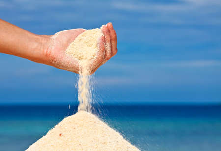 Hand is pouring coral sand on a beach Stock Photo