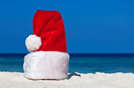 Santa hat is on coral sandy beach photo