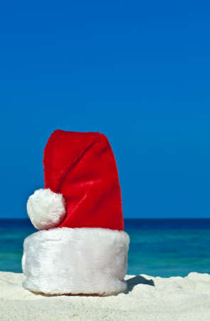 Santas hat is on coral sandy beach photo