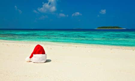 Santa hat is on coral sandy beach