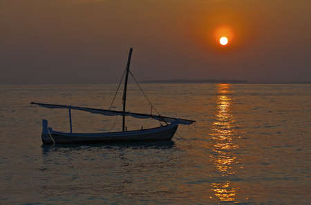 Small sail boat on a sunset, Maldives Stock Photo - 13220055