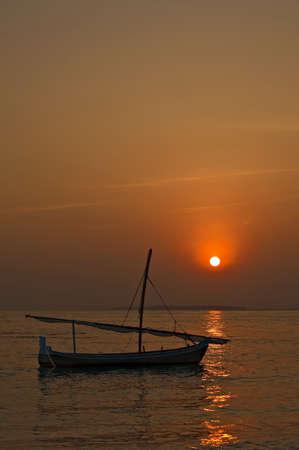 Small sail boat on a sunset, Maldives Stock Photo - 13220031