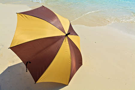 Opened umbrella is on the ocean beach Stock Photo - 19085324
