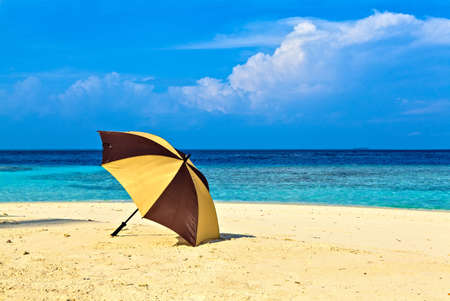 Opened umbrella is on the ocean beach Stock Photo - 19137151