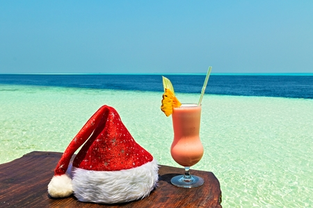 Bocal of drink is on a beach table with Santa hat (Maldives, The Indian Ocean)