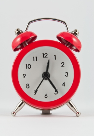 Small red alarm clock on white background photo